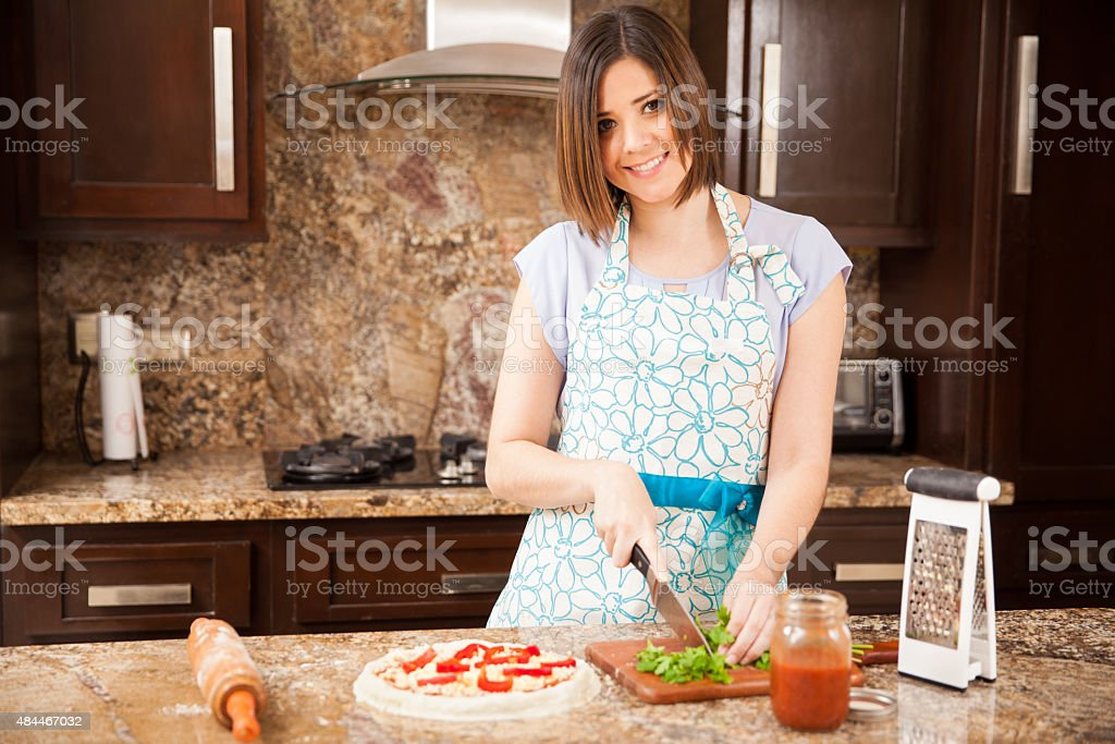 Pretty girl making a pizza and smiling stock photo