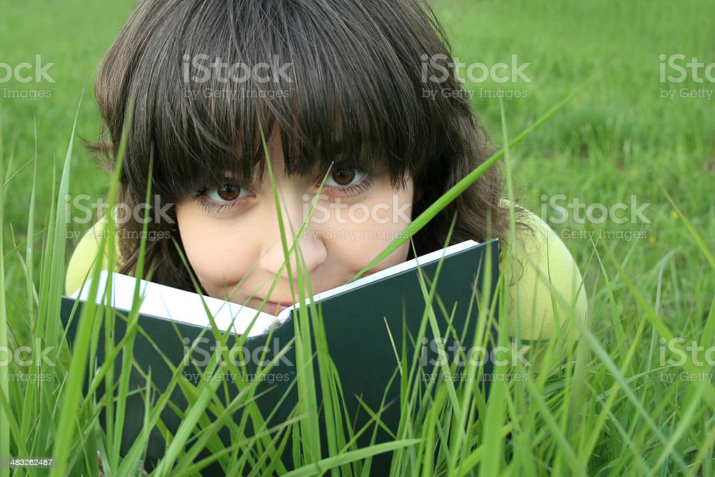 Pretty girl on a grass looking over the book stock photo