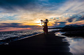 Pretty girl playing a harp on sunset at the seaside.
