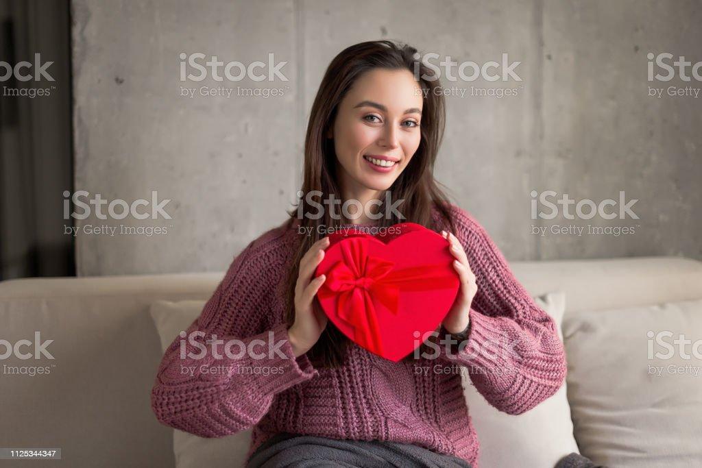 Portrait of a smiling beautiful brunette girl in a purple sweater...
