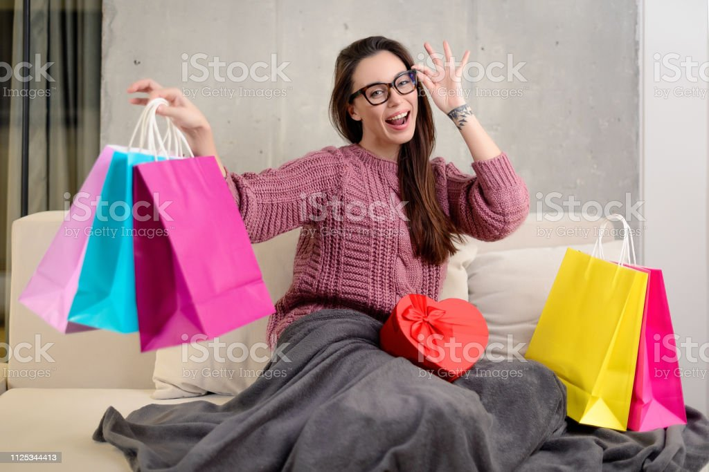portrait of a happy young brunette woman in glasses holding colorful...