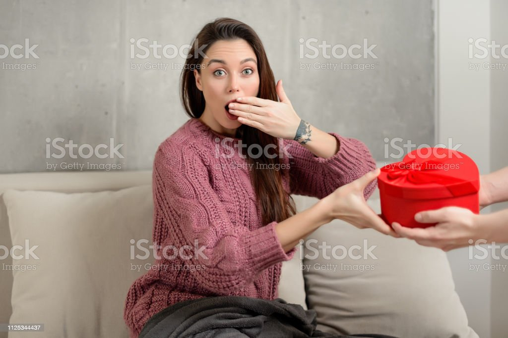 portrait of a happy surprised young brunette girl receiving a...