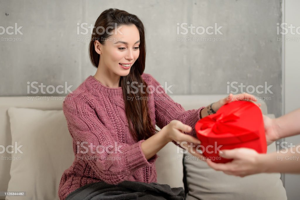 portrait of a happy young brunette girl receiving a heart-shaped...