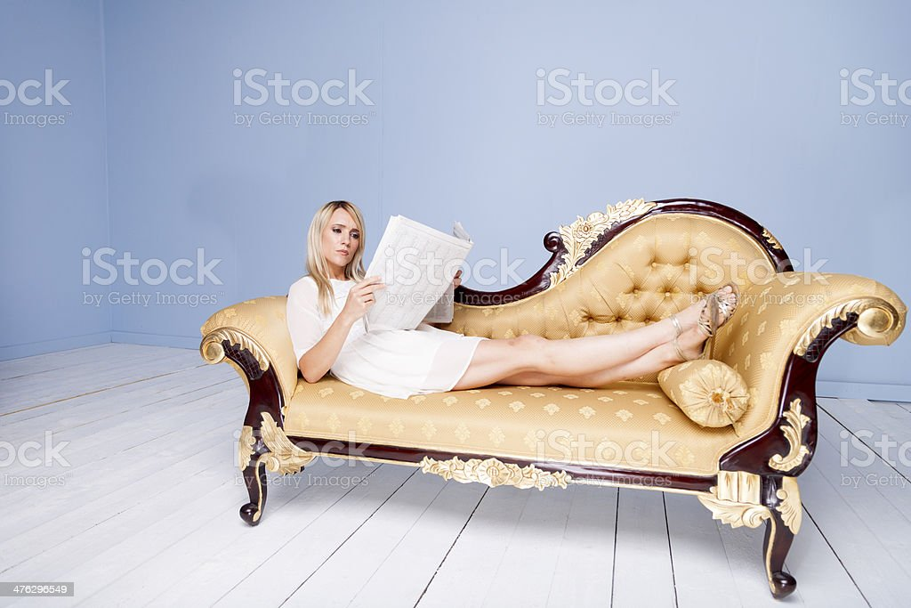 Pretty Girl Reclining And Reading Her Newspaper royalty-free stock photo