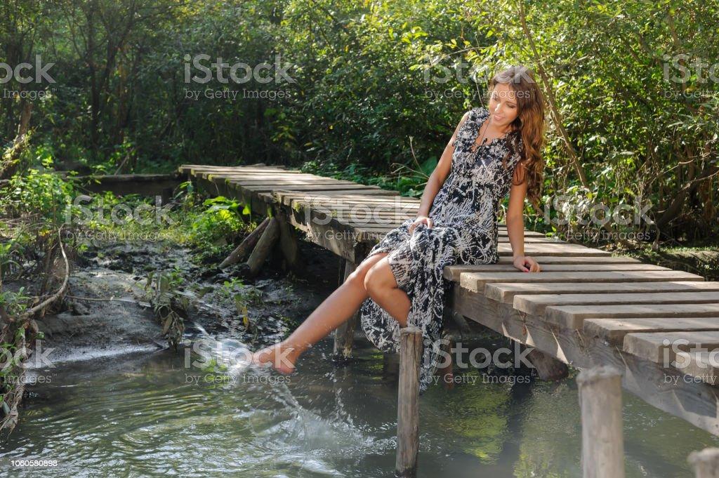 Pretty girl relaxes on pedestrian bridge