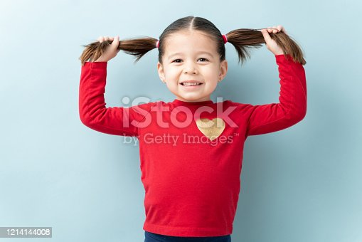 Gorgeous little three year old girl holding up her ponytails and smiling in a studio