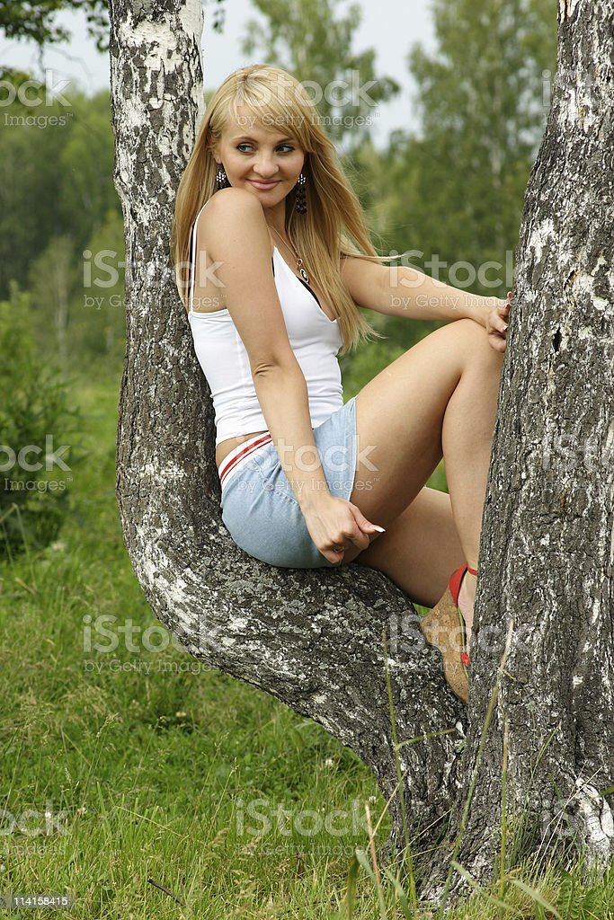 Pretty girl sit on birch in a park. stock photo