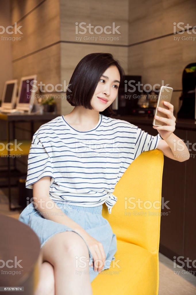 jolie fille assise sur le canapé à l'aide de smartphone dans le salon photo libre de droits