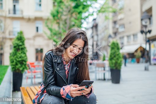 istock Pretty girl smiling and looking into the phone 1159579709