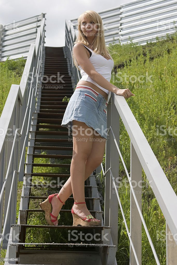 Pretty girl stands on a stairs. royalty-free stock photo
