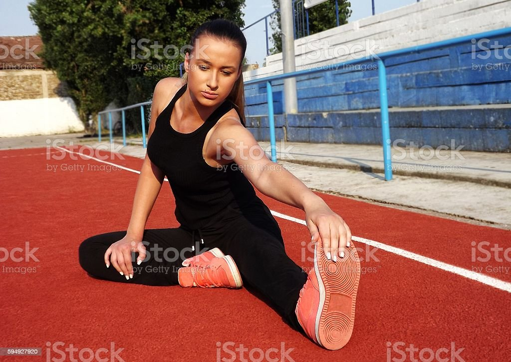 Pretty girl stretching after workout on public court stock photo