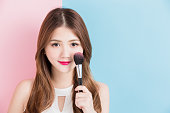 pretty girl take makeup brush in white dress isolated on a pink and blue background