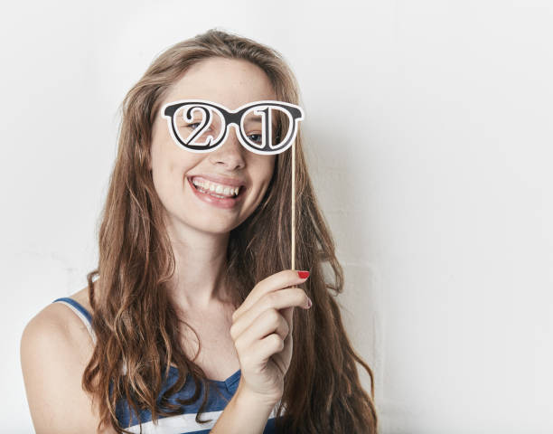 """pretty girl tries on """"21"""" fancy dress spectacles - number 21 stock photos and pictures"""