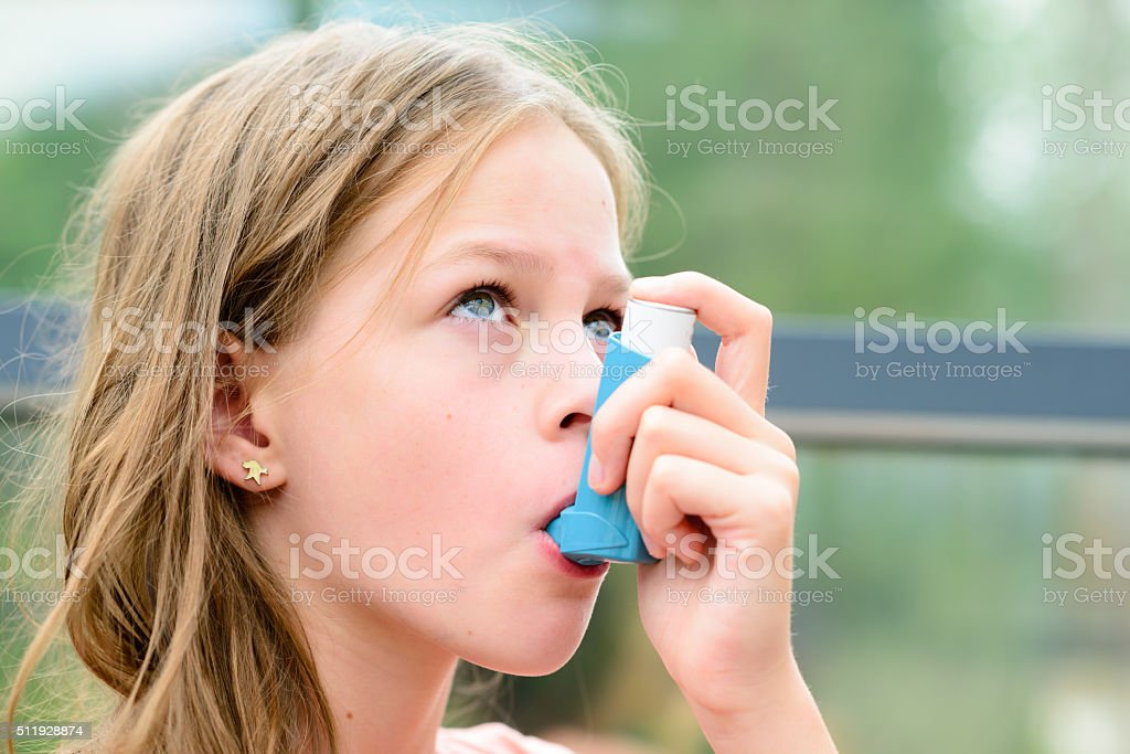 Pretty girl using asthma inhaler stock photo
