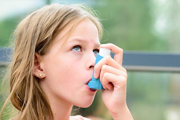 pretty girl using asthma inhaler - astmatisk bildbanksfoton och bilder