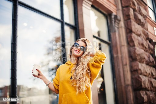 870648602 istock photo Pretty girl wearing sunglasses and bracelets smiling on the street. Outdoor portrait of laughing blonde young woman in mustard sweetshot standing near store. 870648624