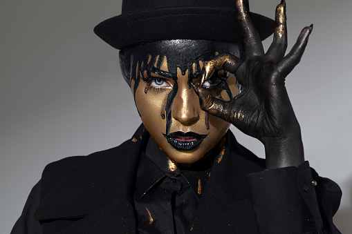 pretty girl with art gold make up an black hat and clothes crying