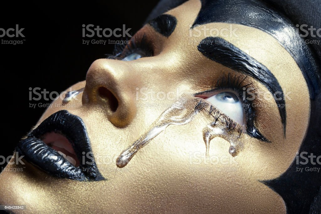 pretty girl with art gold make up and black bros and lips stock photo