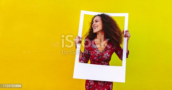 Happy young woman with curly hair looking away through a blank photo frame. Pretty girl with big picture frame against yellow background.