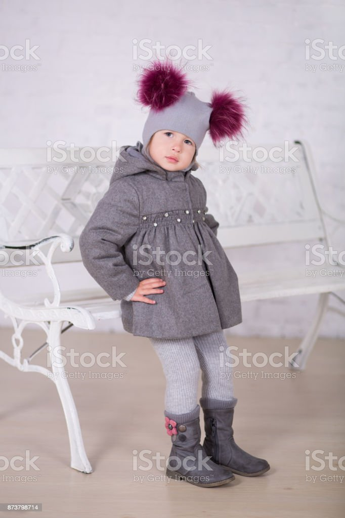 Pretty girl with brunnete hair stylish dressed in gray jacket and warm winter hat happyly smiling posing to camera for photosession in modern showroom studio wearing baby boots. stock photo