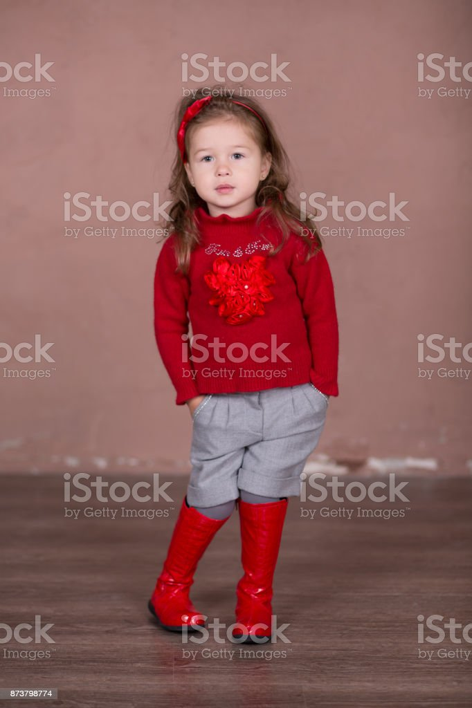 Pretty girl with brunnete hair stylish dressed in red sweater pullover warm winter shorts pants happyly smiling posing to camera for photosession in modern showroom studio wearing baby boots. stock photo