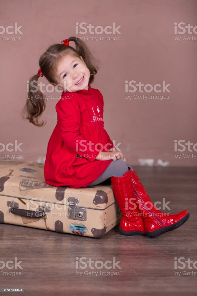 Pretty girl with brunnete hair stylish dressed red long shirt dress with cornrow happyly smiling posing camera photosession modern showroom studio wearing baby boots sitting standing travelling trunk. stock photo
