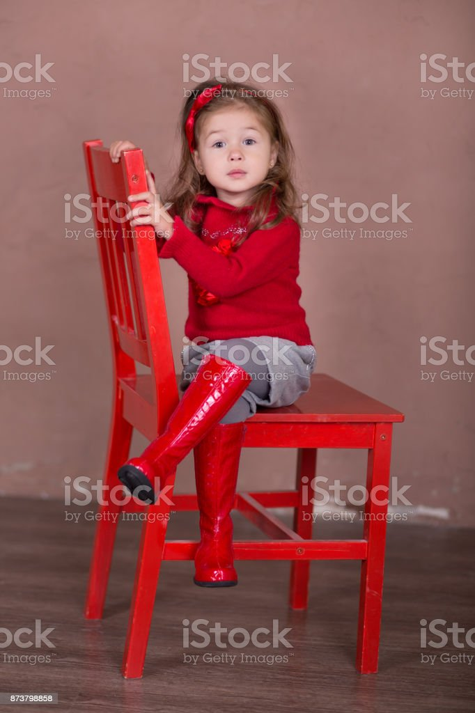 Pretty girl with brunnete hair stylish dressed red sweater pullover warm winter shorts pants happyly smiling posing camera photosession in modern showroom studio wearing baby boots sitting on chair. stock photo