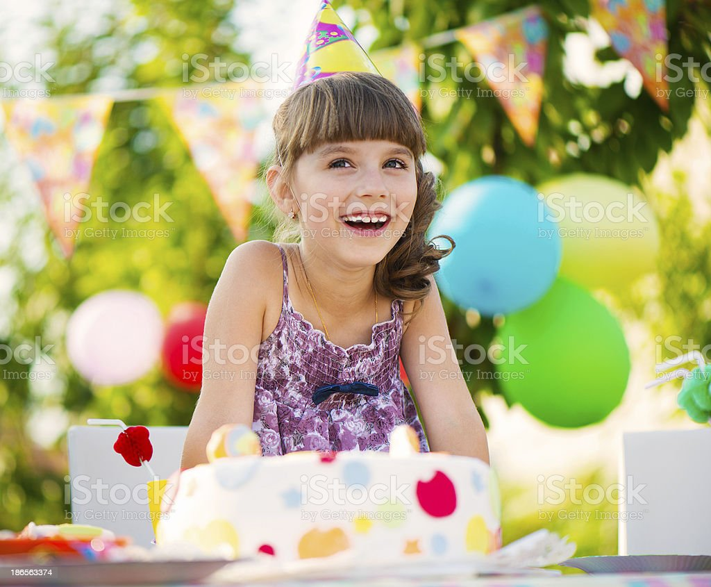 Pretty girl with cake at birthday party stock photo