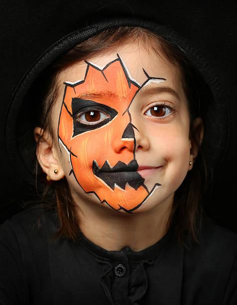 hübsches mädchen mit face painting von einem kürbis - teufel schminken stock-fotos und bilder