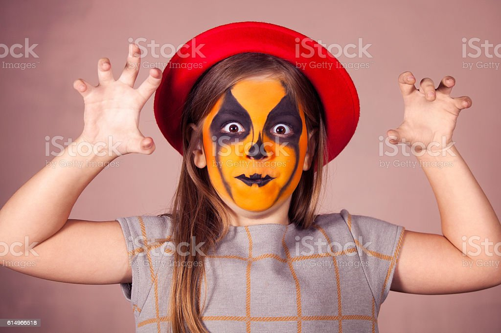 Pretty girl with face painting of a pumpkin - Stock image .