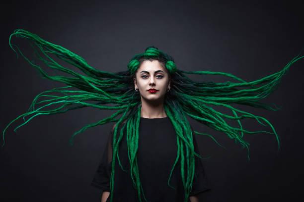 hübsches mädchen mit grünen lange dreadlocks. schwarzer hintergrund. - rote dreads stock-fotos und bilder