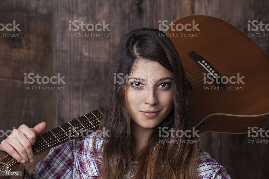 Pretty girl with guitar on shoulder royalty-free stock photo