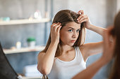 Millennial girl with hair loss problem looking in mirror at home