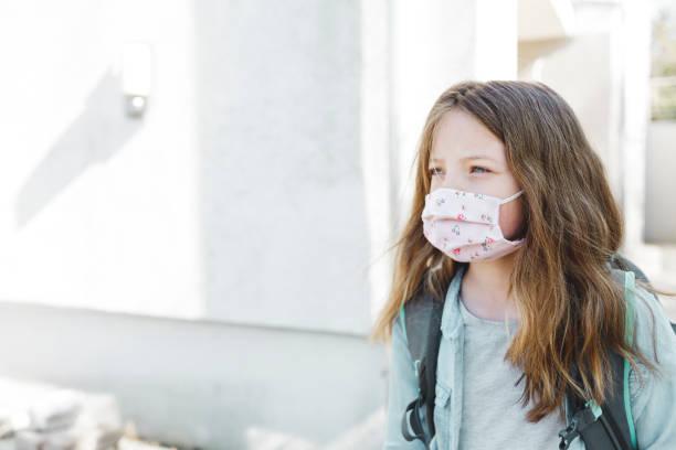 hübsche Mädchen mit Nase Mund Maske geht zur Schule – Foto