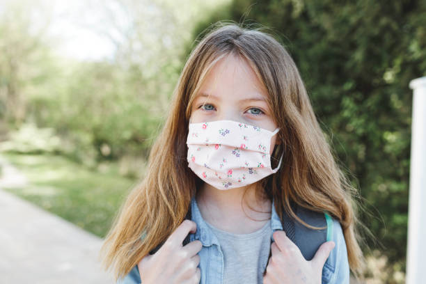 pretty girl with nose mouth mask goes to school stock photo