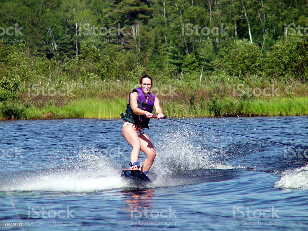 Pretty Girl with Purple lifejacket on wakeboard royalty-free stock photo