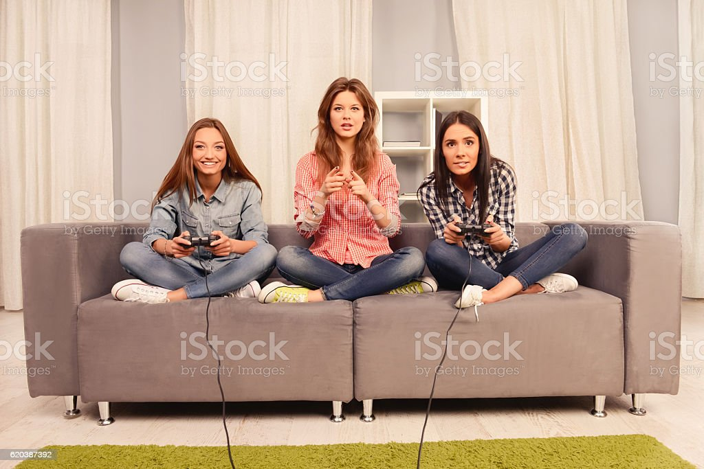 Pretty girls sitting on couch and playing video games - foto de acervo