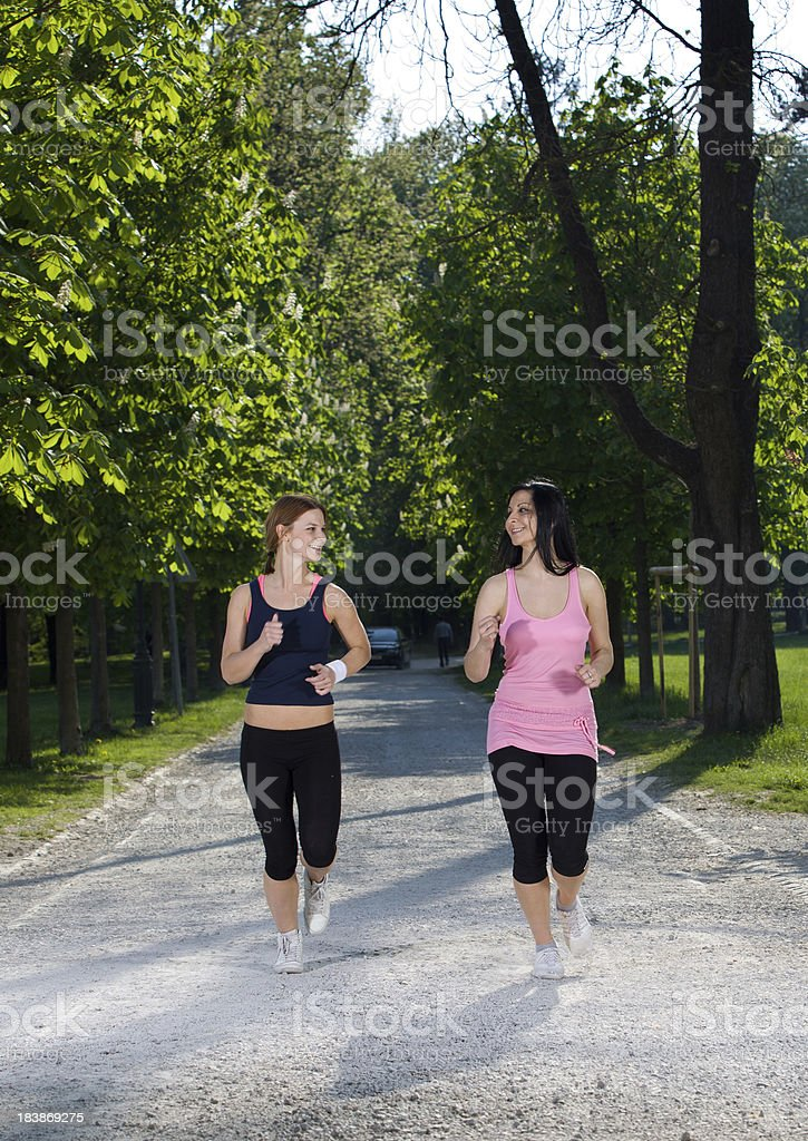 Pretty girls wearing Exercise Clothing jogging in a city park... stock photo
