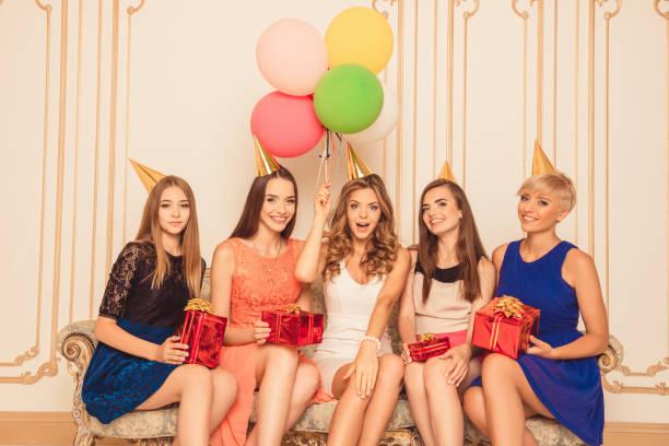 pretty girls with balloons holding birthday presents sitting on - jugendliche geburtstag geschenke stock-fotos und bilder
