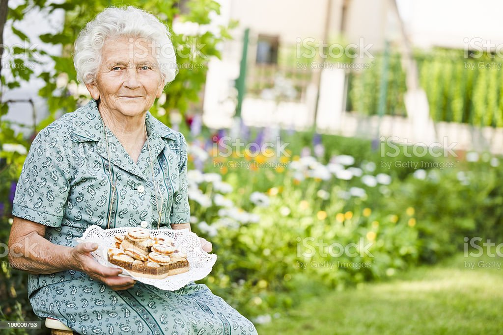 Pretty grandmother holding a plate full of cakes royalty-free stock photo