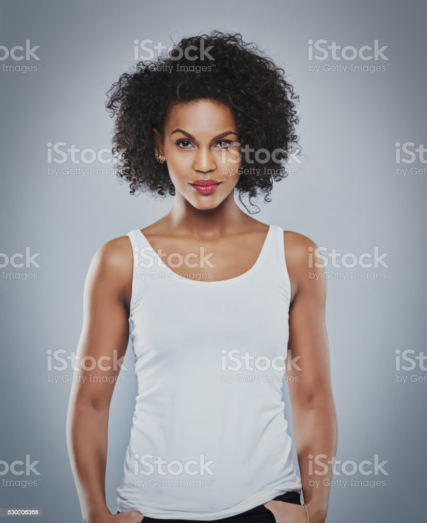 Pretty grinning woman with thumbs in pockets stock photo