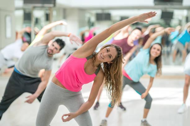 Hübsche gymnastikausbilder Führung ihrer Klasse, alle schauen sehr glücklich zu Strecken – Foto