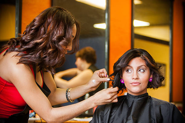 Pretty Hairdresser Styling Beautiful Customer's Hair stock photo