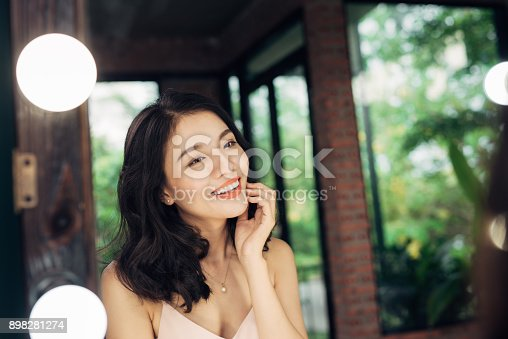 Pretty happy asian woman watching on herself in a big mirror at home.