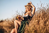 Pretty happy blonde in dirndl, traditional festival dress, sitting with two mugs of beer outdoors in the field with blurred background. Oktoberfest, St. Patrick's day, international beer day concept.