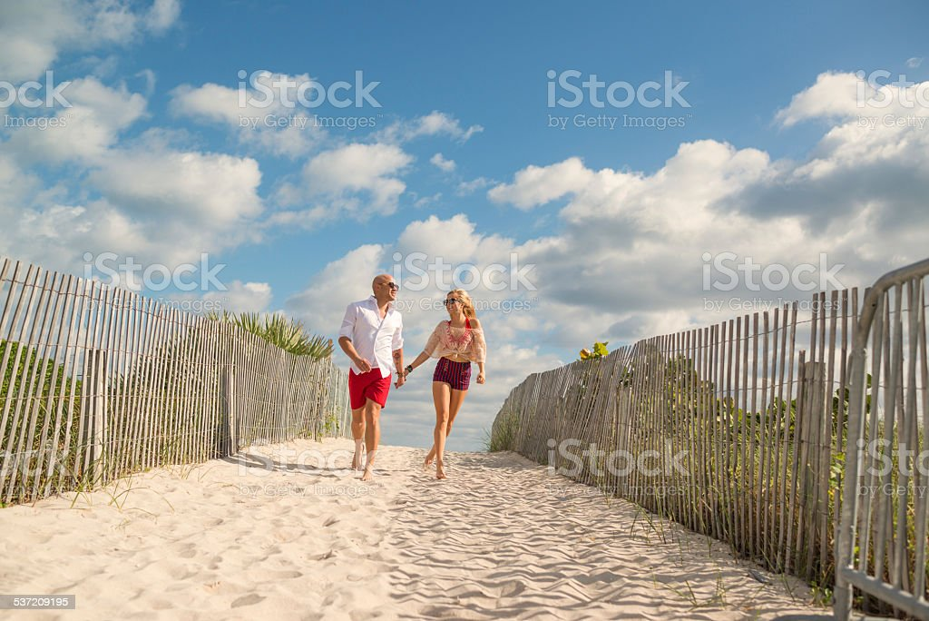 Pretty happy couple going to the beach stock photo