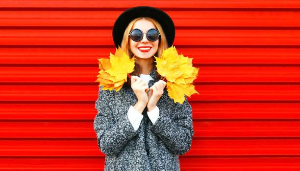 Sehr glückliches Mädchen hält, dass gelbe Ahornblätter auf rotem Grund – Foto