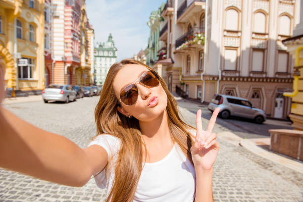 Pretty happy girl in glasses making selfie, showing v-sign and pouting Pretty happy girl in glasses making selfie, showing v-sign and pouting puckering stock pictures, royalty-free photos & images