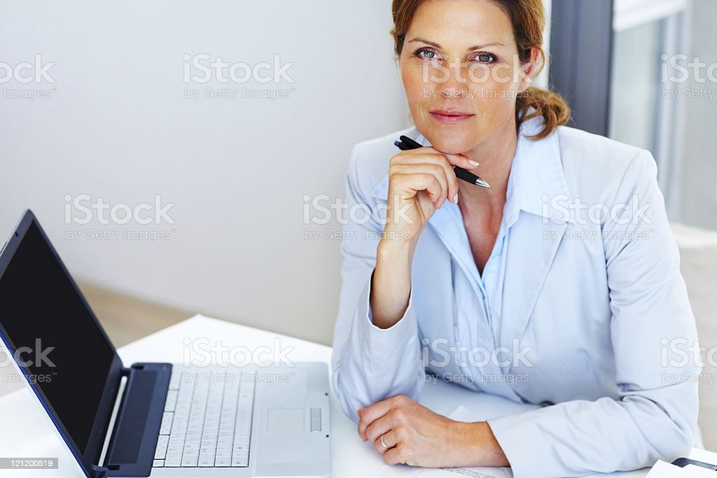 Pretty happy mature lady thinking while at work royalty-free stock photo