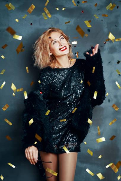Mujer bastante feliz lanzando confeti y bailando disfrutando de la fiesta - foto de stock